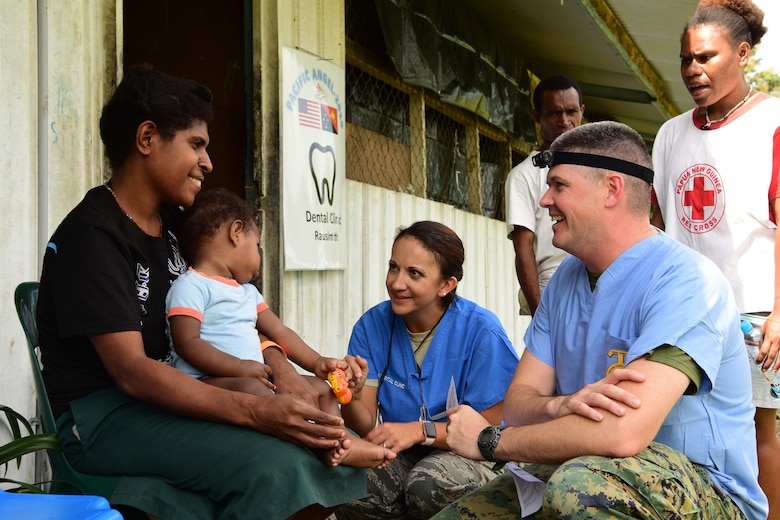U.S. Navy LT Austin Stokes and U.S. Air Force Maj. Nicole Smith, both Pacific Angel 19-4 dentists, talk to a patient at the PAC ANGEL 19-4 health outreach site in Lae, Papua New Guinea Sept. 8, 2019. The health outreach site is comprised of five clinics including primary care, optometry, dental, physical therapy and pharmacy. (U.S. Air Force photo by Tech. Sgt. Jerilyn Quintanilla)