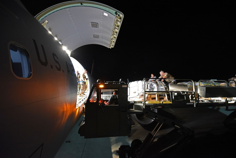 U.S. Airmen from the 60th Aerial Port Squadron from Travis Air Force Base, California, load cargo onto a McConnell AFB, Kansas, KC-46 Pegasus Aug. 21, 2019. The KC-46's stop at Travis entailed a late-night load of life rafts and other cargo for the U.S. Navy's USS Port Royal. (U.S. Air Force photo by Senior Airman Christian Conrad)