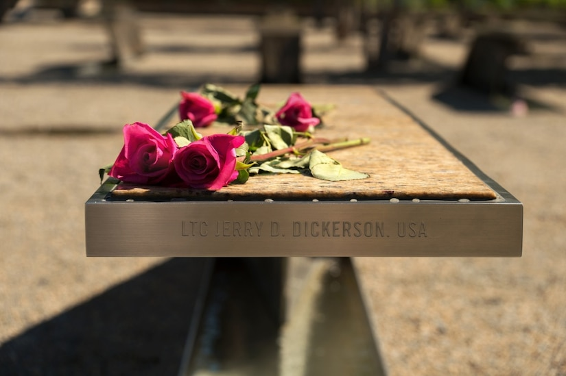 Flowers rest on an engraved bench at the National Pentagon 9/11 Memorial.