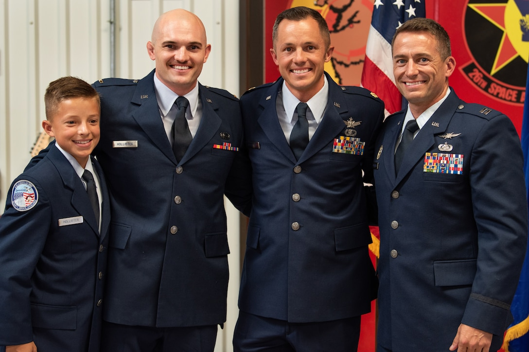 The three Hollister brothers, Taylor (second from left), Scott (middle), Ryan and Scott's son, Trey (left), pose for a photo together during Scott's promotion ceremony Sept. 8, 2019.