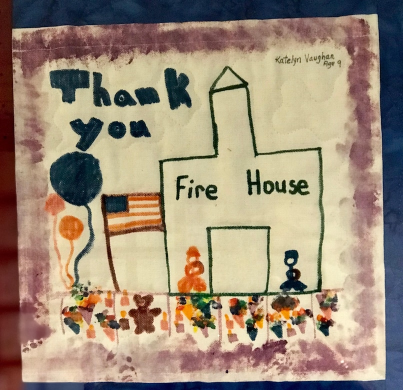 """A poster made by children depicts a firehouse, and U.S. flag, firefighters and the words """"thank you."""""""