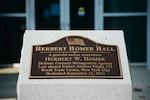 Brass plaque naming a large office building Herbert Homer Hall