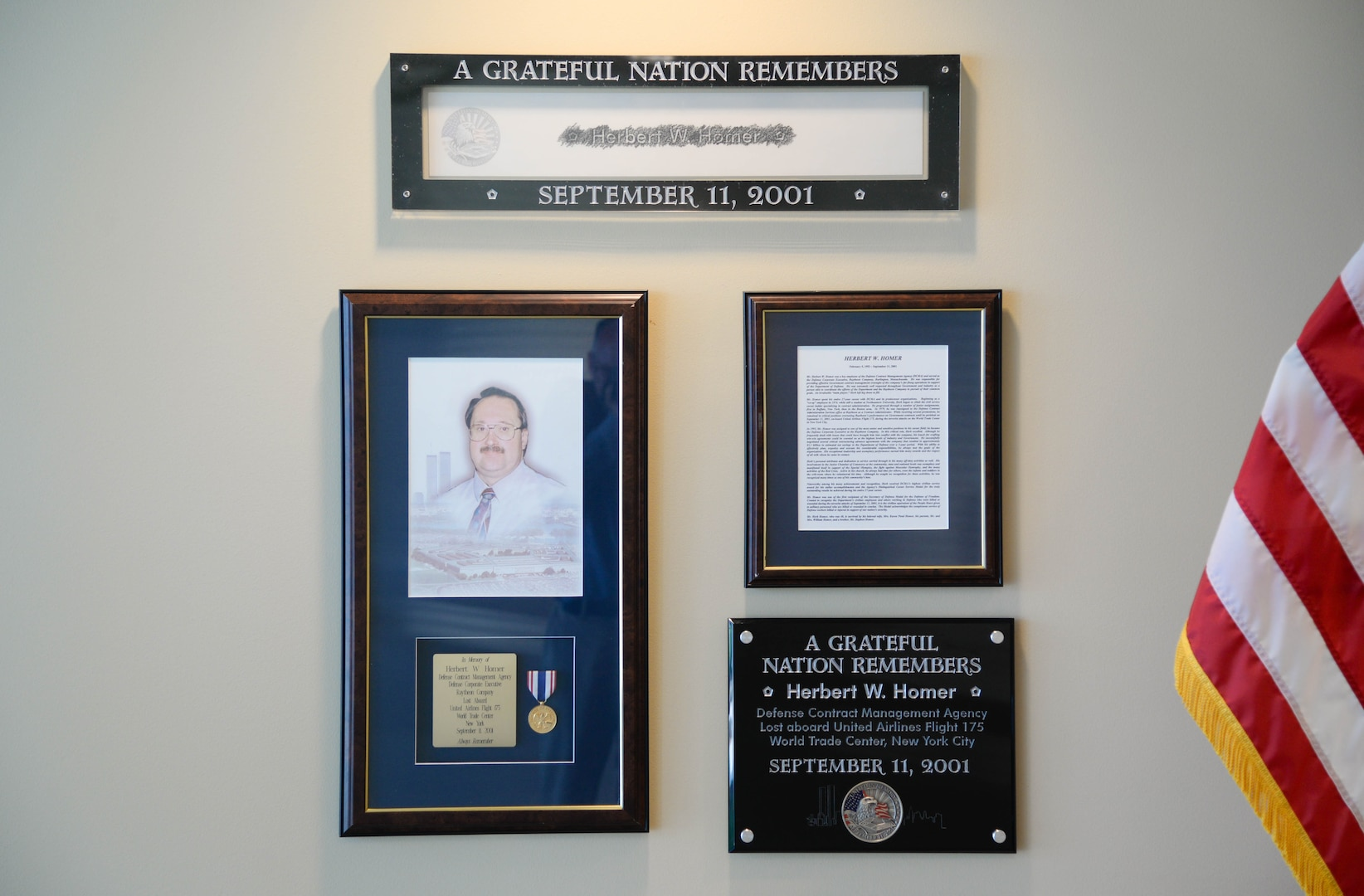 collection of photos and framed letters on a wall