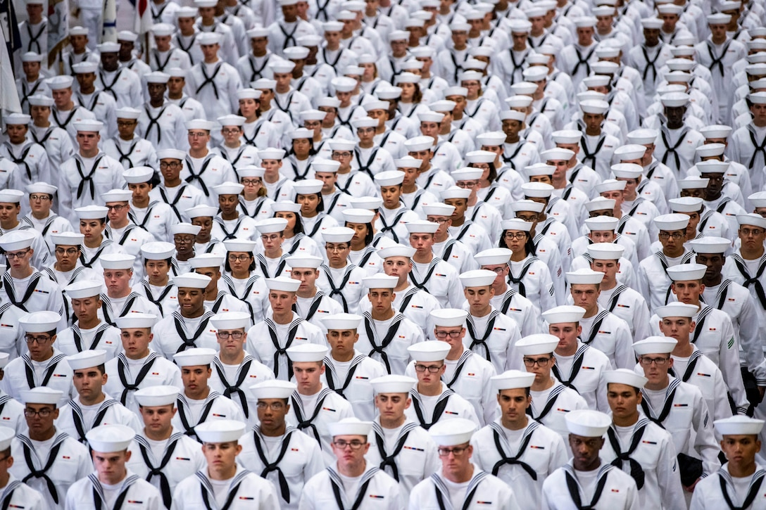 A large group of sailors stand together in rows.