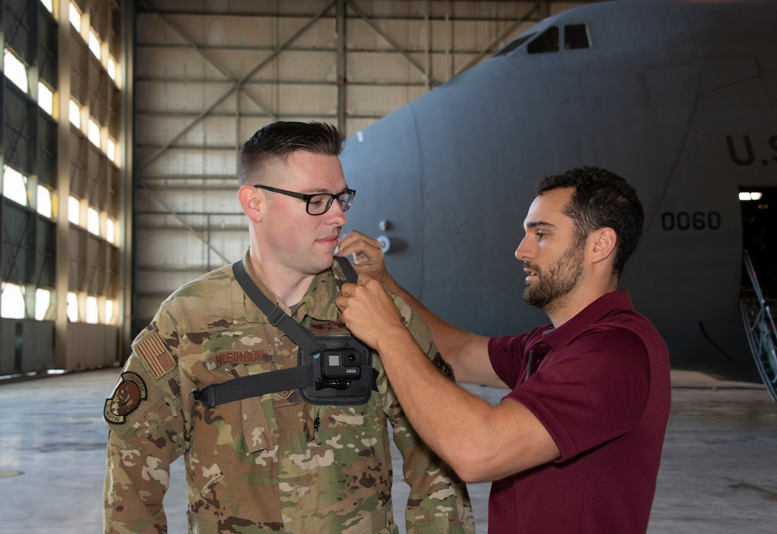 Joe Connolly, head of product for Sketchbox3D, adjusts the straps of a GoPro camera on U.S. Air Force Staff Sgt. Kevin Robinson, 22nd Airlift Squadron loadmaster evaluator Sept. 6, 2019, at Travis Air Force Base, California. The 22nd AS is partnering with Sketchbox3D to develop virtual reality training on C-5M Super Galaxy emergency escape slide egress procedures. (U.S. Air Force photo by Heide Couch)