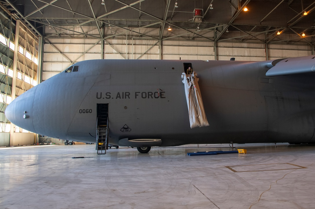 U.S. Air Force Staff Sgt. Kevin Robinson, 22nd Airlift Squadron loadmaster evaluator, deploys a C-5M Super Galaxy emergency escape slide Sept. 6, 2019, at Travis Air Force Base, California. Robinson wore a GoPro camera to record the process which will be used to develop a virtual reality training program on aircraft procedures. (U.S. Air Force photo by Heide Couch)