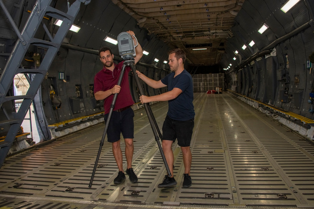 Joe Connolly, left, head of product and Peter Le Bek, engineering manager with Sketchbox3D, use 3D laser scanning technology to image a C-5M Super Galaxy cargo bay Sept. 6, 2019, at Travis Air Force Base, California. Sketchbox3D is working with the 22nd Airlift Squadron and Travis Phoenix Spark cell to develop virtual reality training on aircraft procedures. (U.S. Air Force photo by Heide Couch)