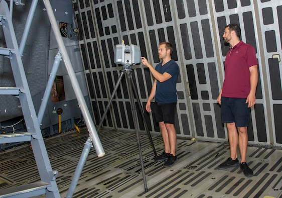 Peter Le Bek, left, engineering manager and Joe Connolly, head of product for Sketchbox3D, use 3D laser scanning technology to image a C-5M Super Galaxy cargo bay Sept. 6, 2019, at Travis Air Force Base, California. Sketchbox3D is working with the 22nd Airlift Squadron and Travis Phoenix Spark cell to develop virtual reality training on aircraft procedures. (U.S. Air Force photo by Heide Couch)
