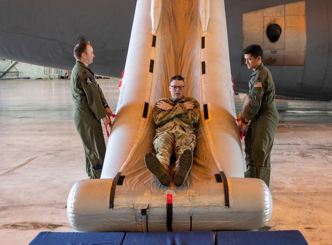 U.S. Air Force Capt. Drew Pagenkopf, left,  tactics flight commander, and Capt. Jose Hinojosa, right, C-5 evaluator aircraft commander, both with the 22nd Airlift Squadron watch as Staff Sgt. Kevin Robinson, 22 AS loadmaster evaluator, uses a C-5M Super Galaxy emergency escape slide Sept. 6, 2019, at Travis Air Force Base, California. Robinson wore a Go Pro camera to record footage of the process to be used to develop a virtual reality training program on aircraft procedures. (U.S. Air Force photo by Heide Couch)
