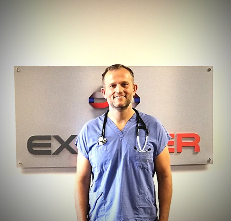 Dr. Nathaniel Ott, an Air Force Reserve instructor in Air University's LeMay Center Joint Integration directorate, stands in his scrubs at his civilian-capacity career as an ER physician in Odessa, Texas. Ott was on-scene during a mass-shooting incident in Odessa on Aug. 31, 2019, and provided life-saving first-aid to a victim who had sustained three gunshot wounds while in her vehicle.