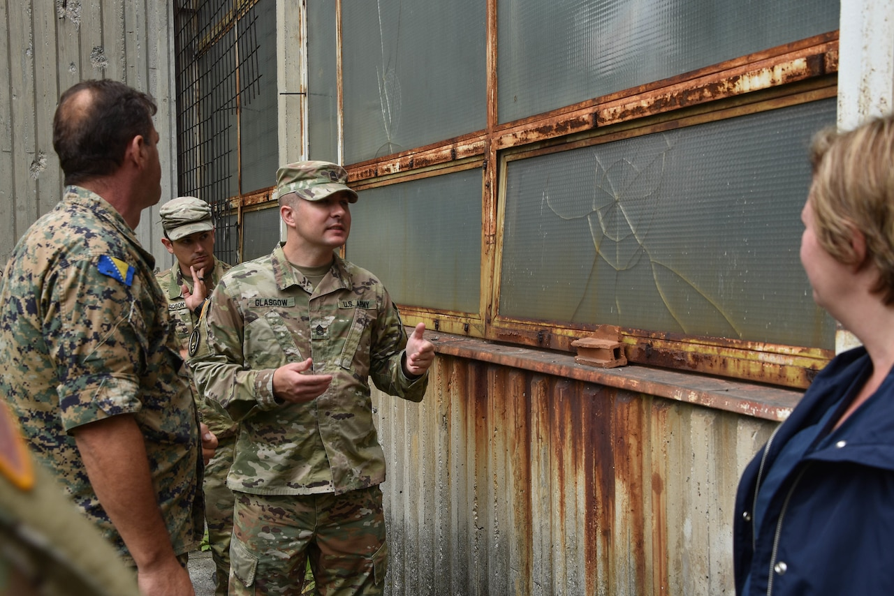 Three service members stand outside a rusty building.