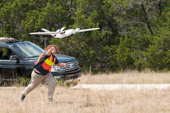 Ethan Jacobs, unmanned aerial system engineer, launches a UAS during a field test Sept. 4 at Camp Bullis, Texas. The UAS was equipped with Light Detection and Ranging, multi-spectral sensors and machine-learning algorithms to map, survey and inventory habitat for the golden-cheeked warbler. The field test will help the Air Force determine if UAS technology can characterize habitat better, faster and cheaper than current methods.