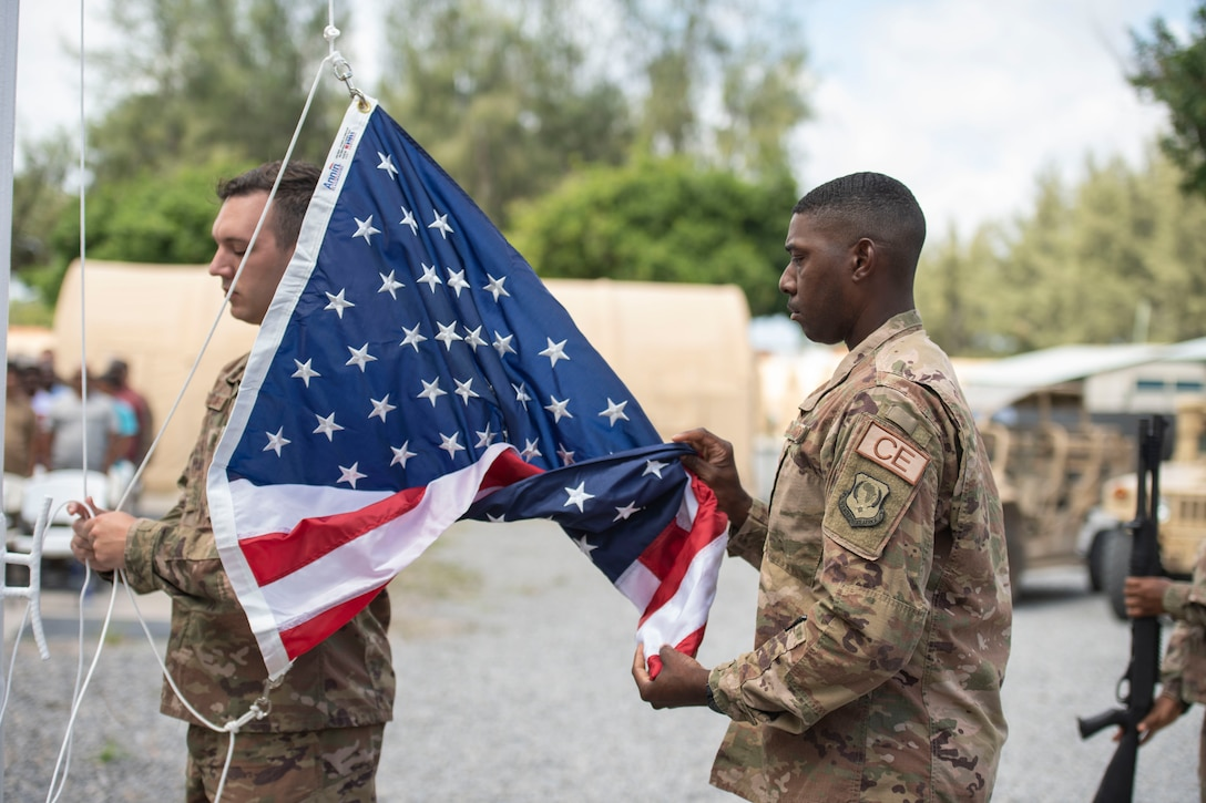 U.S. Air Force Staff Sgt. Sidney Dellinger, 475th Expeditionary Air Base Squadron materiel management journeyman, and Staff Sgt. Corey Smith, 475th EABS heating, ventilation, and air conditioning non-commissioned officer in charge, perform flag detail during a ceremony at Camp Simba, Kenya, Aug. 26, 2019. The 475th EABS raised the flag for the first time since the base operating support-integrator mission started in 2017, signifying the change from tactical to enduring operations. (U.S. Air Force photo by Staff Sgt. Lexie West)