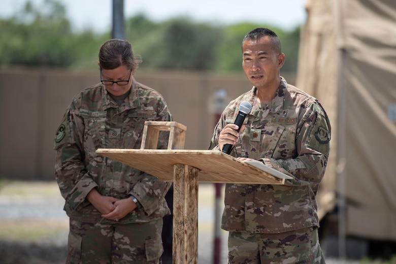 U.S. Air Force Maj. Hoang Nguyen, 435th Air Expeditionary Wing chaplain, gives an invocation while Master Sgt. Shannon Brady, 475th Expeditionary Air Base Squadron first sergeant, bows her head during a flag-raising ceremony at Camp Simba, Kenya, Aug. 26, 2019. The 475th EABS raised the flag for the first time since the base operating support-integrator mission started in 2017, signifying the change from tactical to enduring operations. (U.S. Air Force photo by Staff Sgt. Lexie West)