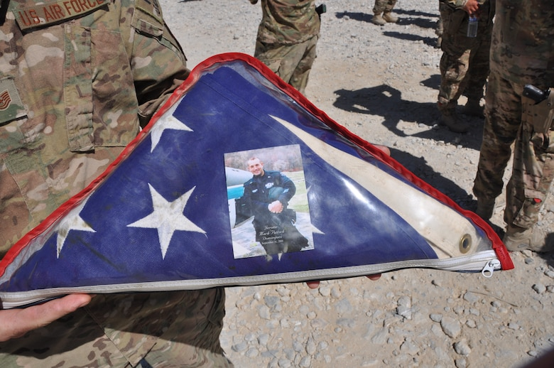 Folded US flag with a photo of Staff Sgt. Jerome Dominguez.
