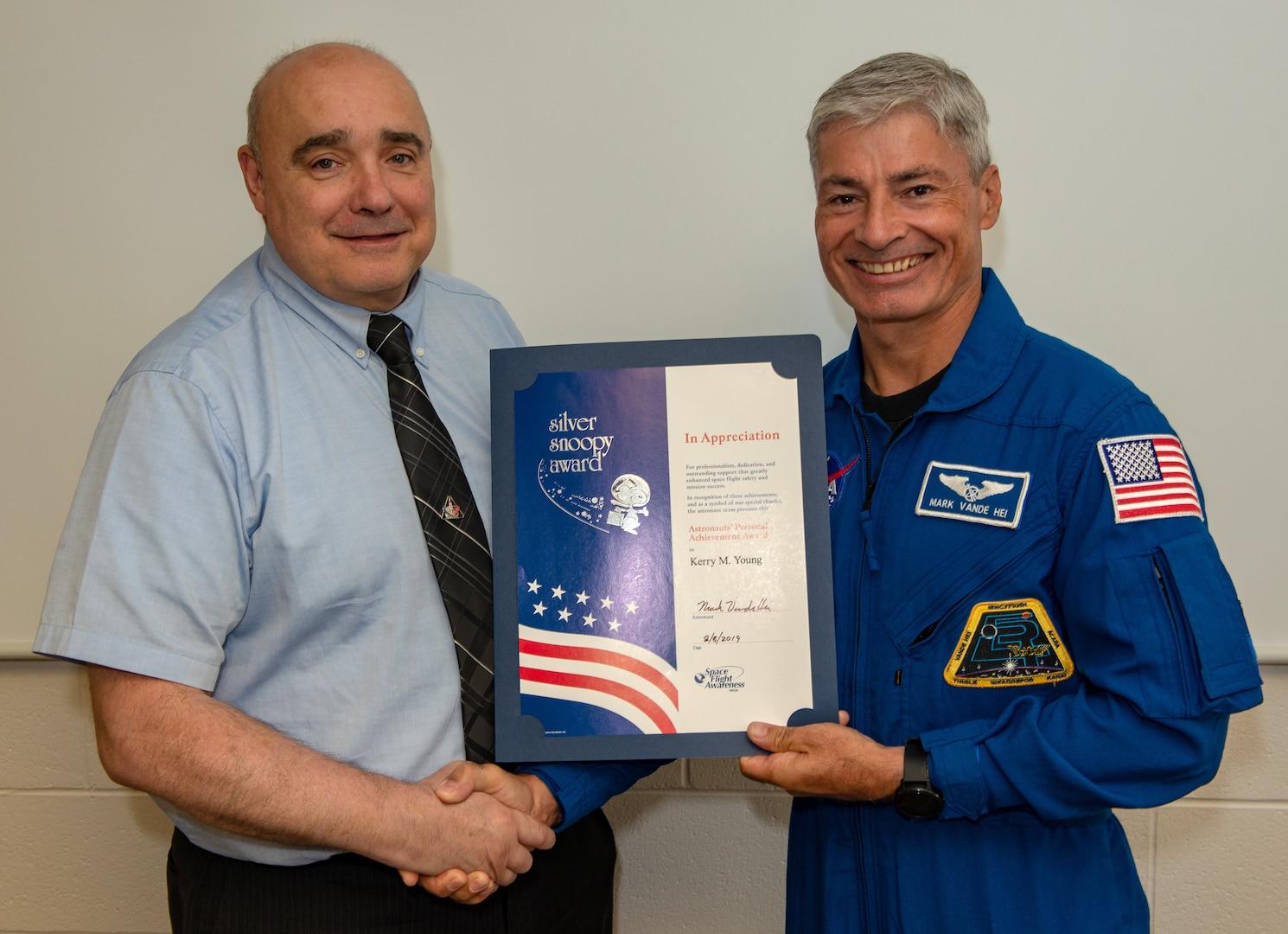A man in a blue astronaut uniform hands a certificate to another man