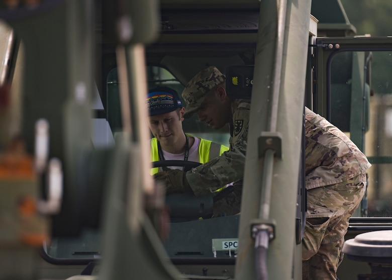 A U.S. Army Soldier teaches a Port of Virginia dockworker how to operate a vehicle during training for a cargo transportation exercise at Fort Story, Virginia, Aug. 20, 2019.