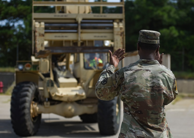 A U.S. Army Soldier guides a Port of Virginia dockworker during training for a cargo transportation exercise at Fort Story, Virginia, Aug. 20, 2019.