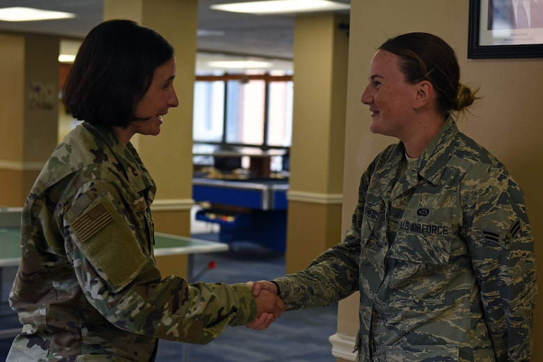 """U.S. Air Force Chief Master Sgt. Summer Leifer, Twenty-Fifth Air Force command chief, left, coins Airman 1st Class Kylie, 32nd Intelligence Squadron, for excellence in performance at Fort George G. Meade, Maryland, Sept. 9, 2019. Kylie is an """"out-of-access"""" Airman currently assisting with dorm operations, and was recognized for leadership, innovation and eagerness to help others. (U.S. Air Force photo by Senior Airman Gerald R. Willis)"""