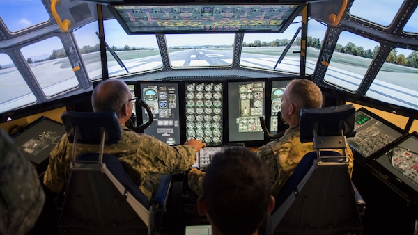 Col. Hugo Parentini, Uruguayan Air Force, and Col. Stephen Gwinn, 103rd Airlift Wing Commander, operate the wing's C-130H Hercules Multi-Mission Crew Trainer (MMCT) during a State Partnership Program visit to Bradley Air National Guard Base, East Granby, Conn. Aug. 15, 2019.