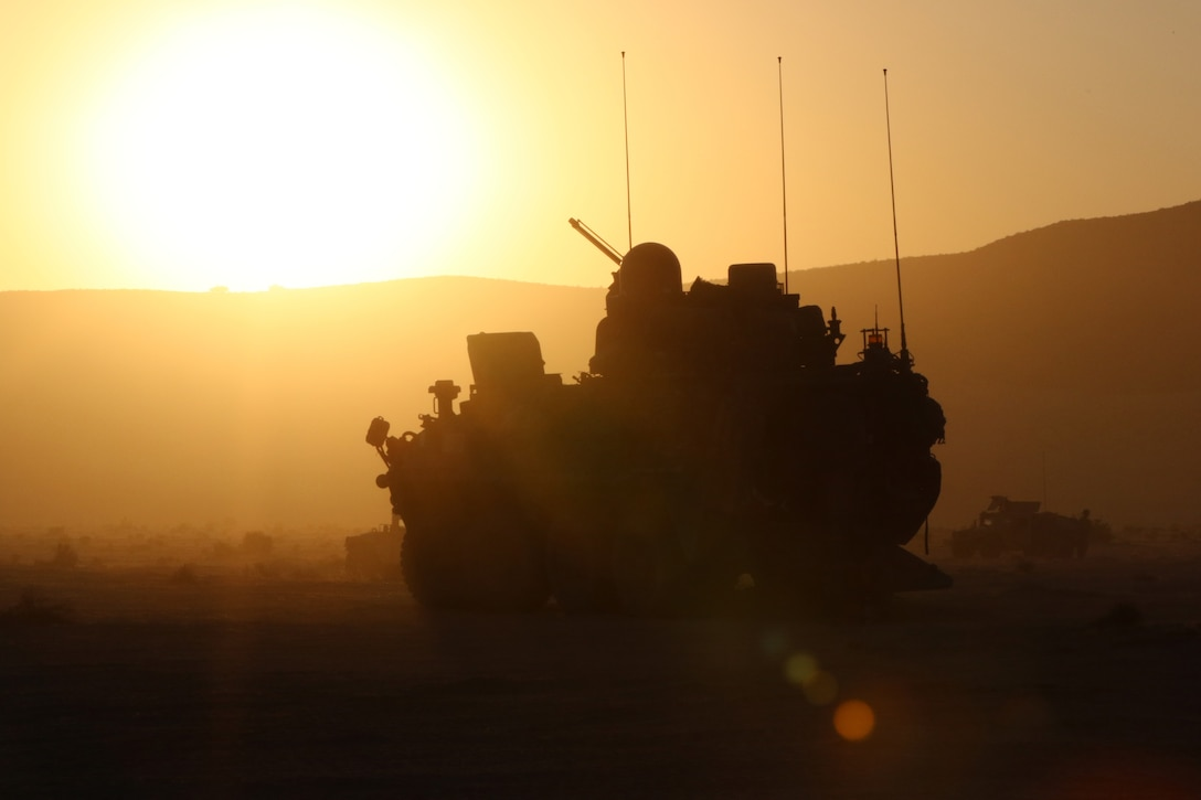 A military vehicle is silhouetted against the sun.