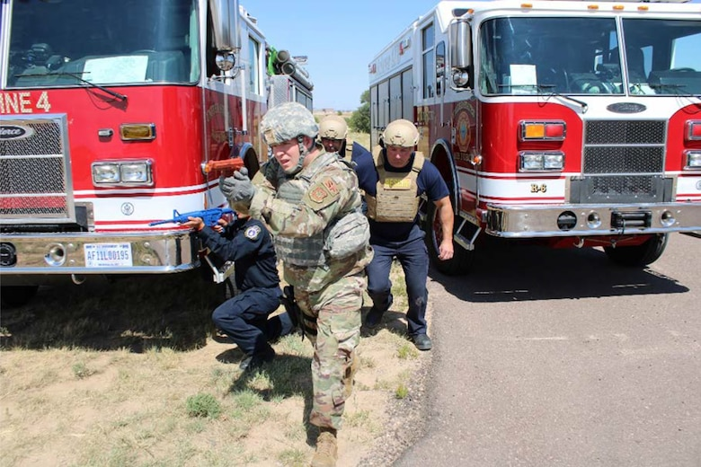 Tech. Sgt. Preston Morgan, 50th Security Forces Squadron response force leader, escorts Schriever AFB firefighters from their staging area into the threat area during an active shooter training scenario at Schriever Air Force Base, Colorado, Aug. 26, 2019. The training provided an opportunity for 50th Civil Engineer Squadron firefighters and 50th SFS defenders to learn about the tactics each unit uses in active shooter situations. (U.S. Air Force photo by Mark Captain)