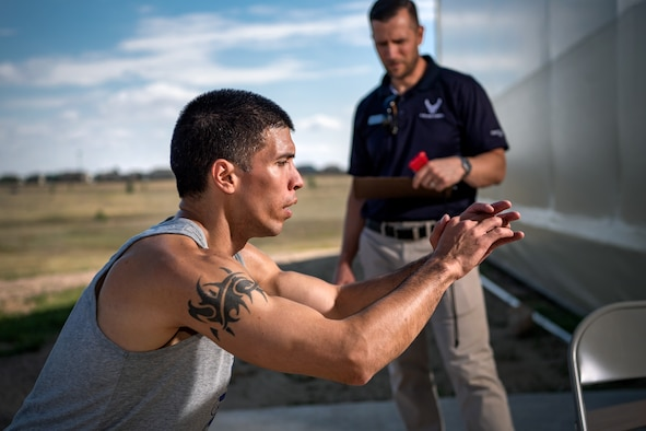 Master Sgt. Joshua Gutierrez, 2nd Space Operations Squadron operations superintendent, focuses on his body-squat form during the DriTri Fitness Competition Sept. 6, 2019, at Schriever Air Force Base, Colorado.