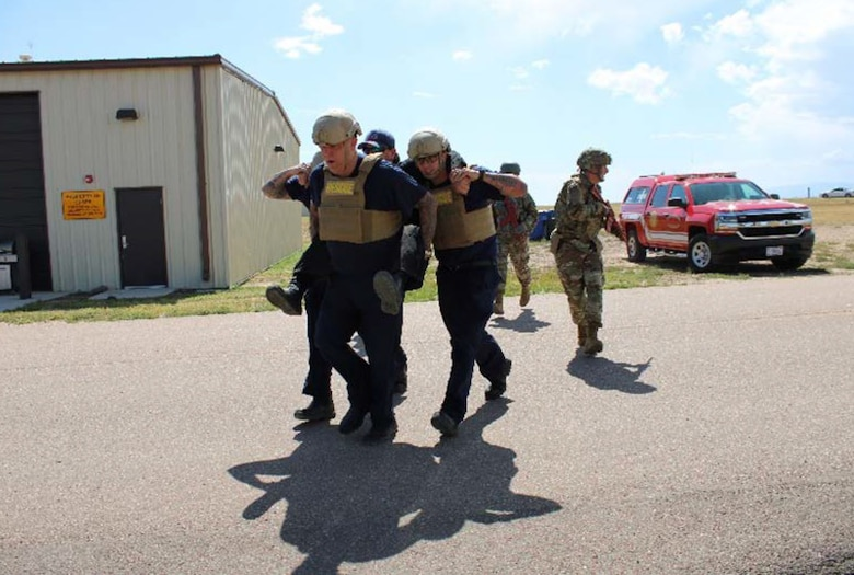 Matt Clark, 50th Civil Engineer Squadron lead firefighter, left, and Mark Crane, 50th CES firefighter driver and operator, transport a victim to safety while escorted by Senior Airman Cody Bilgers, 50th Security Force Squadron standards and evaluation evaluator, during an active shooter training scenario at Schriever Air Force Base, Colorado, Aug. 26, 2019. The exercises conducted in the hands-on portion of the training included practicing various maneuvers to enhance victim response techniques and tactics when entering an area as a team to safely remove the injured. (U.S. Air Force photo by Mark Captain)