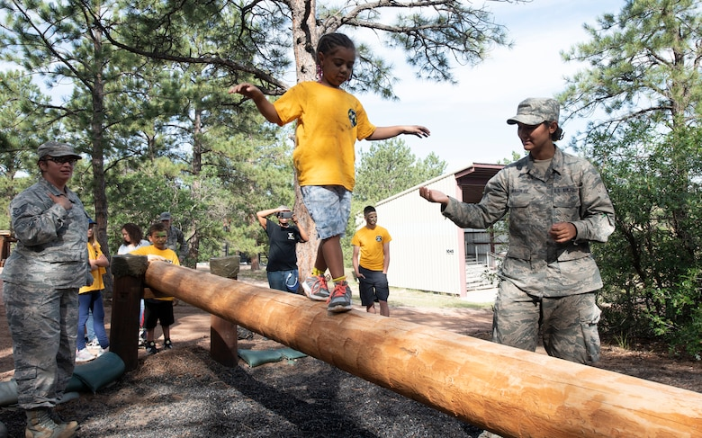 Naelani, 5, navigates the balancing pole during the obstacle course portion of the Kids Understanding Deployment Operations event at U.S. Air Force Academy, Colorado, Sept. 7, 2019. The children were transported to Jack's Valley Training Complex, where they watched a K-9 demonstration, went through a confidence course, learned about Tactical Air Control Party, and had lunch courtesy of the USO. (U.S. Air Force photo by Staff Sgt. Matthew Coleman-Foster)