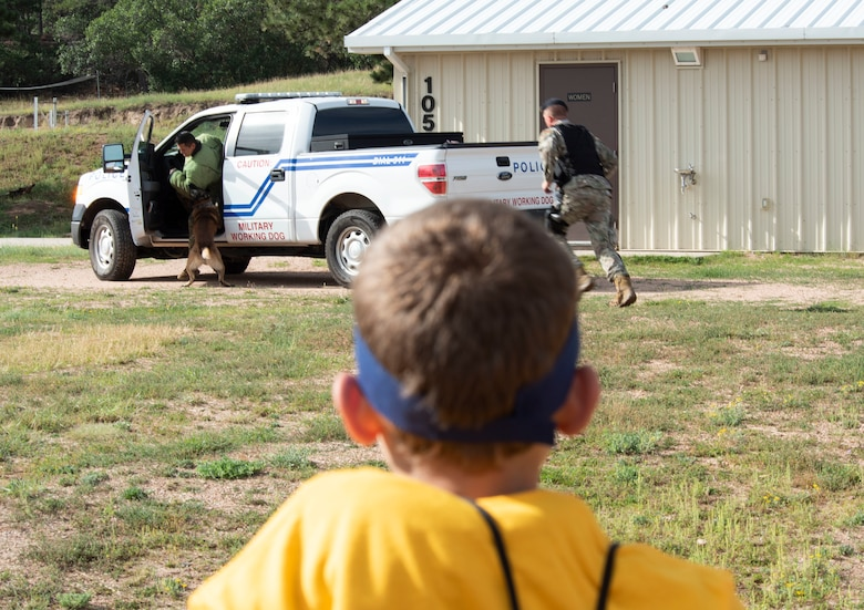 A child watches as K-9 Nick pulls a simulated suspect out of a vehicle during the K-9 demonstration portion of the Kids Understanding Deployment Operations, at Jack's Valley Training Complex, U.S. Air Force Academy, Colorado, Sept. 7, 2019. More than 60 local military, Department of Defense and contractor's children and teens experienced first-hand what their military family members experience when deployed. (U.S. Air Force photo by Staff Sgt. Matthew Coleman-Foster)