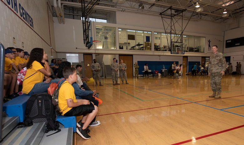 """Col. Brian Hartless, 10th Air Base Wing commander, right, briefs children on what to expect during their """"deployment"""" experience during the in-processing session of the Kids Understanding Deployment Operations event, U.S. Air Force Academy, Colorado, Sept. 7, 2019. The day's events mirrored the stages of an actual deployment process to help children of military members understand what their parents go through when they deploy. (U.S. Air Force photo by Staff Sgt. Matthew Coleman-Foster)"""