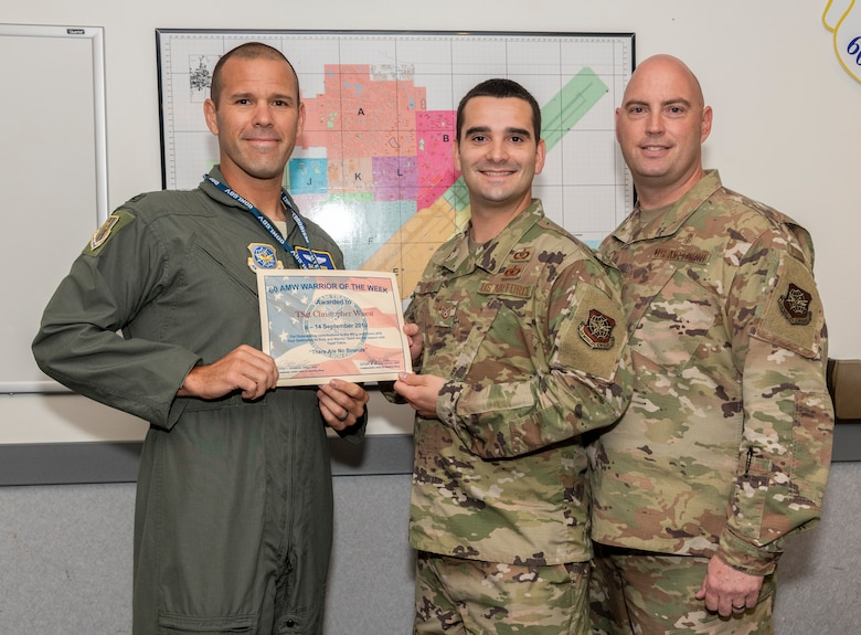 U.S. Air Force Col. Zachery Jiron, left, 60th Air Mobility Wing, vice commander, and Chief Master Sgt. Vincent Brass, right, 60th Medical Group superintendent, recognize Tech. Sgt. Christopher Wuest, 60th AMW Command Post NCO in charge command and control operations reports, as the Warrior of the Week Sept. 10, 2019 at Travis Air Force Base, California. The Warrior of the Week program recognizes an outstanding Travis Airman or noncommissioned officer. (U.S. Air Force photo by Heide Couch)