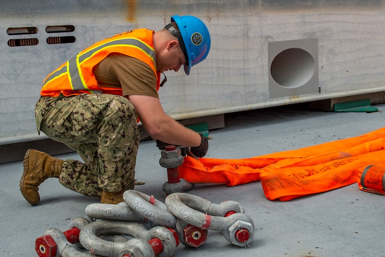 A sailor wearing a hardhat and orange vest kneels on a ship's deck and attaches a metal piece to an orange sling.