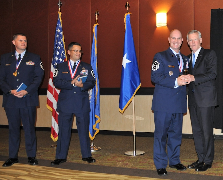 """Retired Lt. Gen. Bruce """"Orville"""" Wright, far right, National Air Force Association President, presents Master Sgt. Benjamin Davis, center right, 50th Mission Support Group 50th Force Support Squadron and Wing Staff Agencies first sergeant, with the 2018 AFA First Sergeant of the Year Award during the 2018 AFA Airmen of the Year awards ceremony at the AFA Mile High, Aug. 17, 2019. The award recognizes Airmen for their outstanding performance and leadership skills and takes into consideration the whole Airman concept to select its nominees. (U.S. Air Force courtesy photo)."""