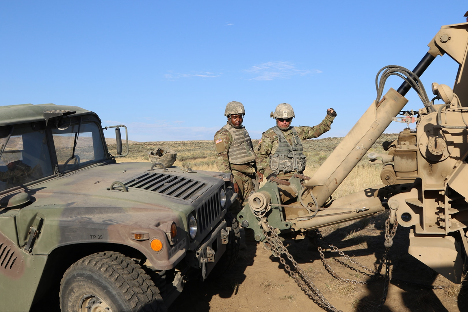 """Sgt. First Class Brian Jackson from the 1844th Transportation Company uses a """"halt"""" hand signal as his recovery vehicle's towbar lines up with the humvee during a training lane in Rising Thunder 2019."""