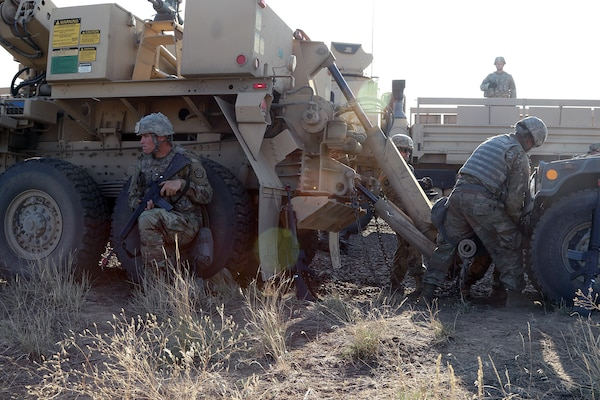Sgt. Brett Montgomery from the 1844th Transportation Company, 108th Sustainment Brigade, pulls security while the maintenance crew hooks up a downed humvee to their recovery vehicle.