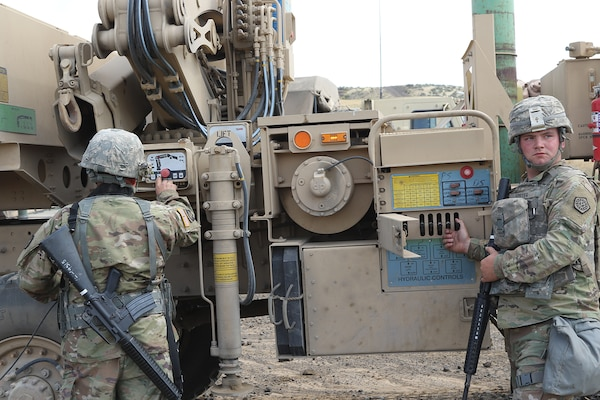 Maintenance Soldiers from the 1844th Transportation Company, 108th Sustainment Brigade work on attaching the recovery vehicle's towbar to a downed truck.