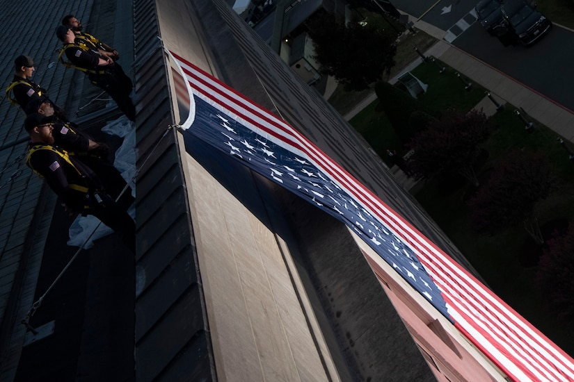 Workers in matching uniforms stand on the Pentagon roof overlooking a giant American flag.