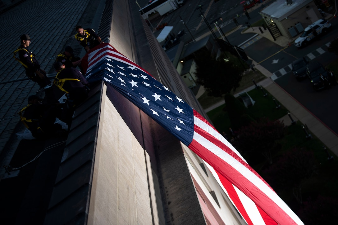 Works on the roof of the Pentagon unfurl a giant  American flag over a side of the building.