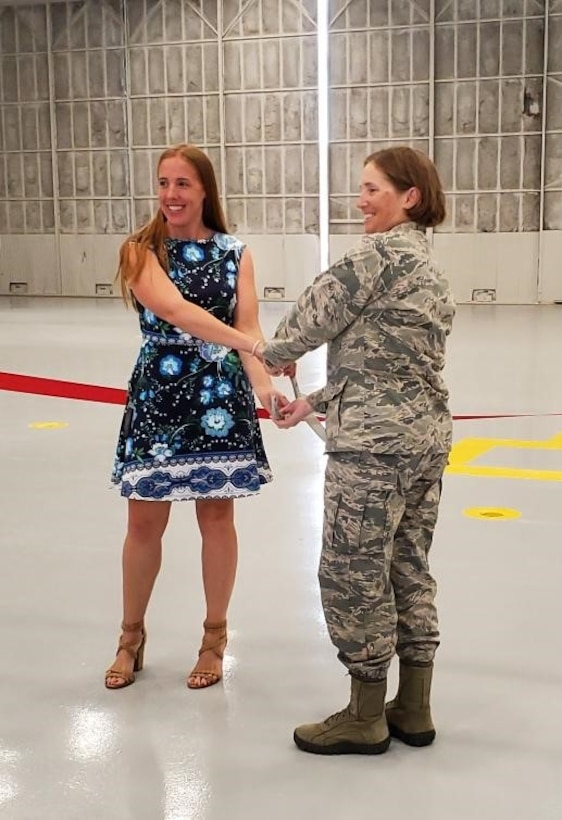 Col. Williams and Ms. Shari Rodgers pose for the first cut of the ribbon to dedicate the new 940th Air Refueling Wing Maintenance Squadron Operations and Inspection Dock.