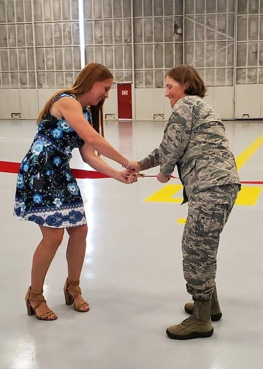 Col. Williams and Ms. Shari Rodgers pose for the first cut of the ribbon to dedicate the new 940th Air Refueling Wing Maintenance Squadron Operations and Inspection Dock. (USAF by Maj. Denise Hauser)