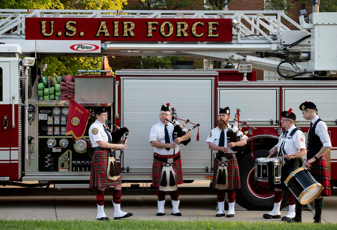 People play bagpipes in front of firetruck