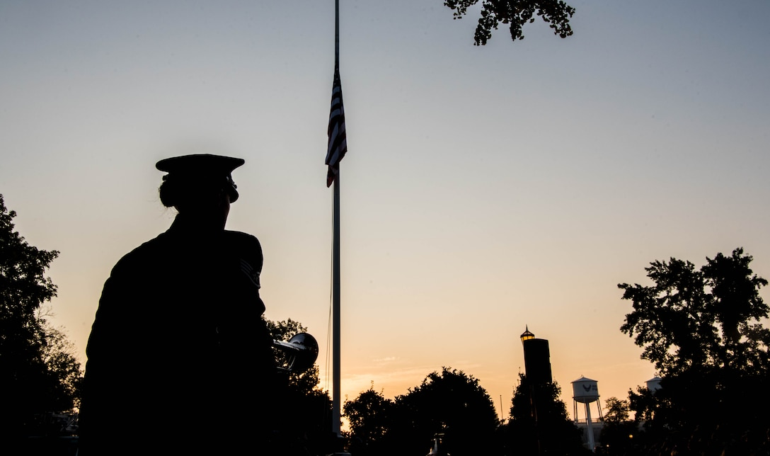 Airman stands in front of flag