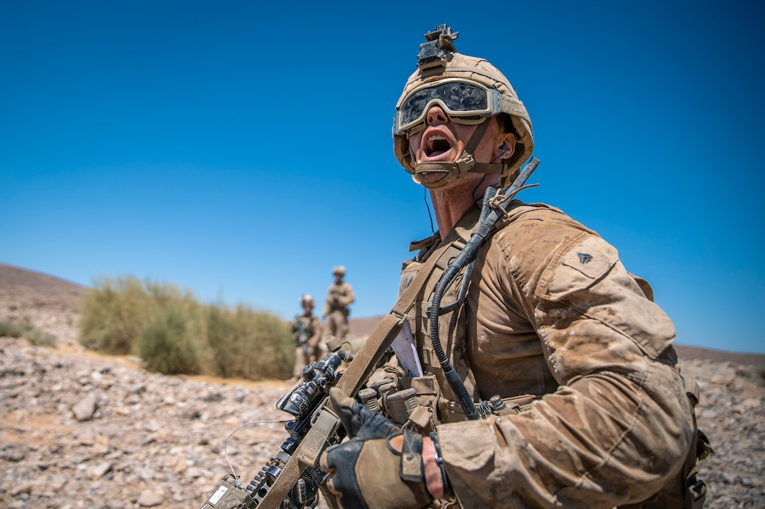 A Marine yells while holding a weapon and standing in desert-type terrain.
