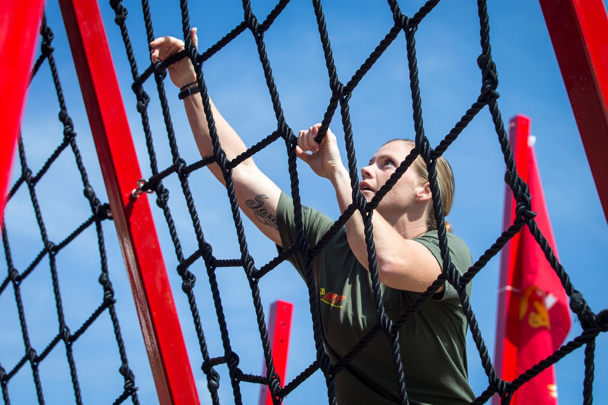 A Marine climbs netting on an obstacle.
