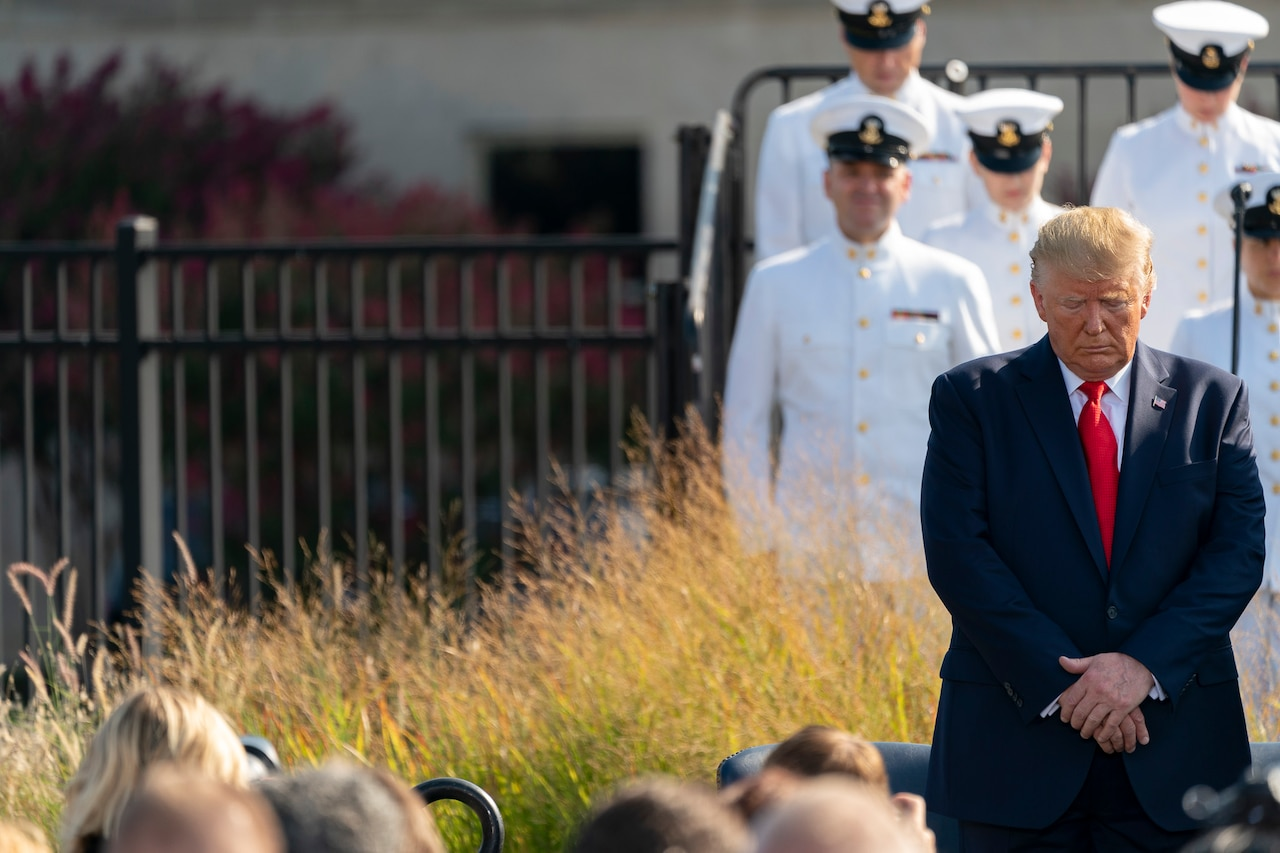 President Donald J. Trump stands with his head down. Military service members in uniform stand in the background.