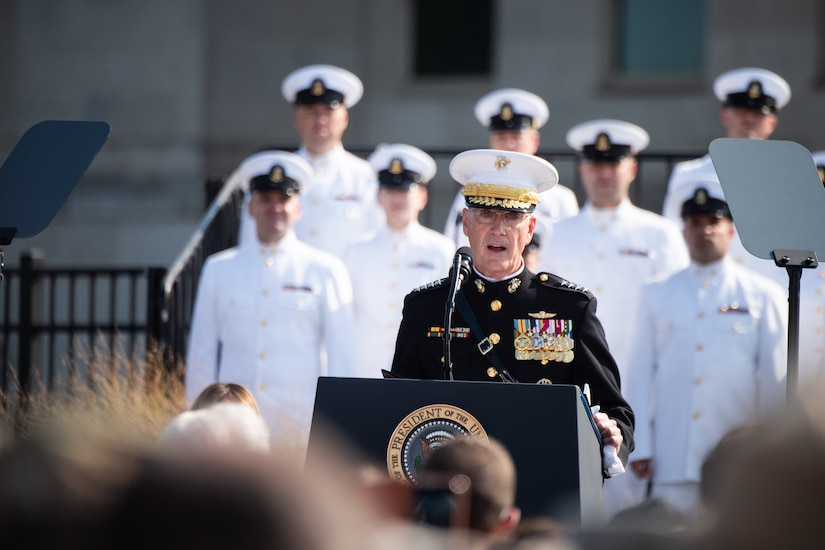 Marine Corps Gen. Joe Dunford, chairman of the Joint Chiefs of Staff, speaks with service members in the back ground.