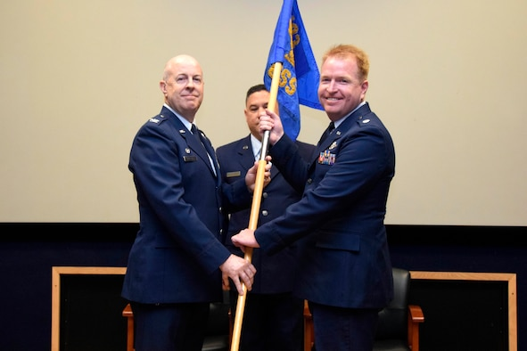 """Lt. Col. Jonathan R. Behunin (right), accepts the guidon from Col. James C. """"JC"""" Miller, 433rd Operations Group commander, during an assumption of command ceremony for the 433rd Operations Support Squadron at Joint Base San Antonio-Lackland, Texas, Sept. 7, 2019."""