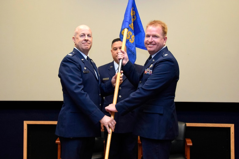 "Lt. Col. Jonathan R. Behunin (right), accepts the guidon from Col. James C. ""JC"" Miller, 433rd Operations Group commander, during an assumption of command ceremony for the 433rd Operations Support Squadron at Joint Base San Antonio-Lackland, Texas, Sept. 7, 2019."