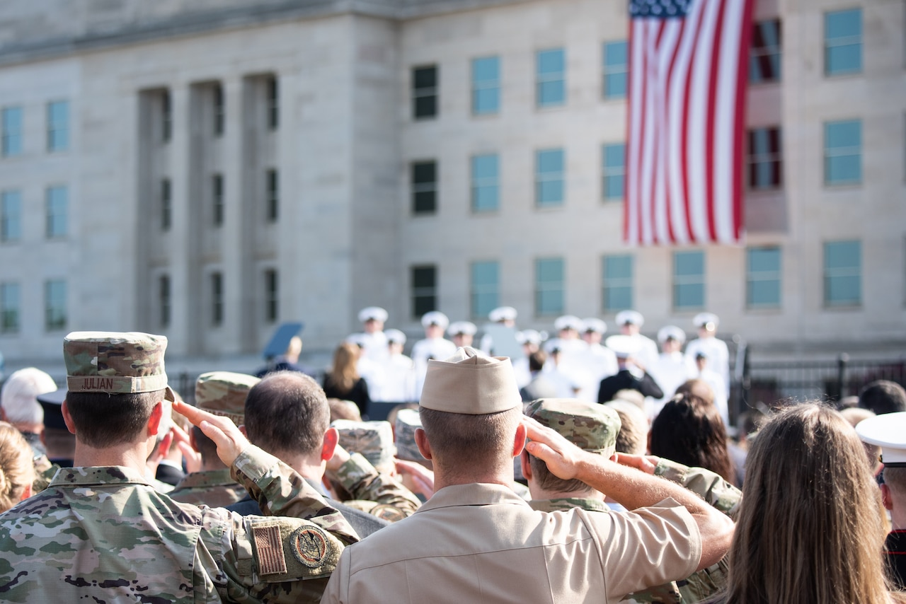 Service members salute toward a flag.